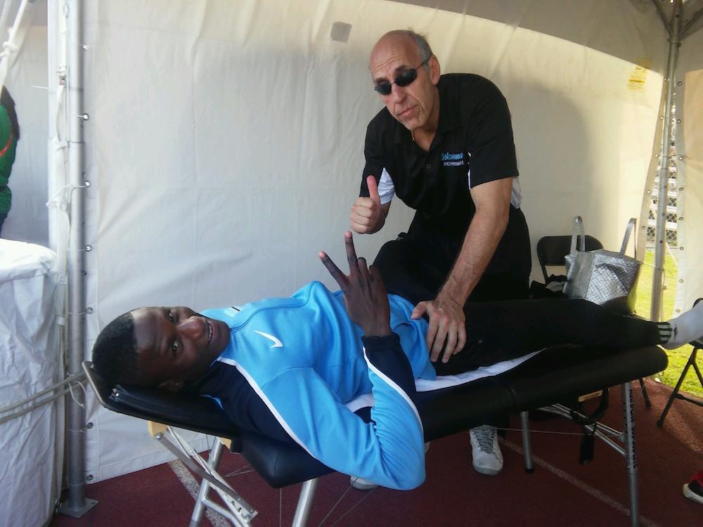 At the World Relays, Dr. Claussen treats a member of the Men's Botswana team prior to a 4 x 400m Silver Medal performance.